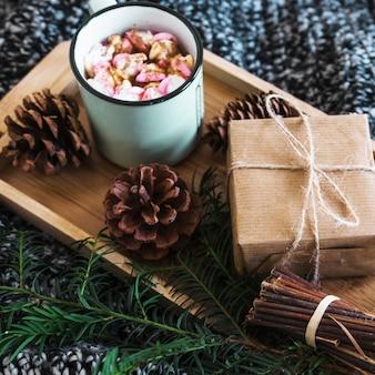 Cones e galho perto de chocolate quente presente na bandeja
