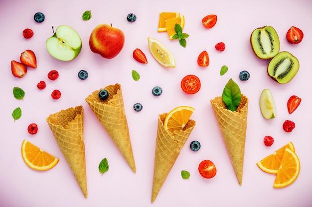Cones e vários frutos coloridos setup no fundo cor-de-rosa.