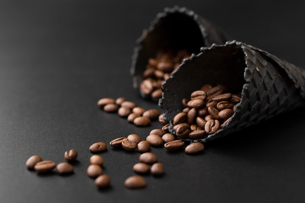 Cones escuros com grãos de café em uma mesa escura