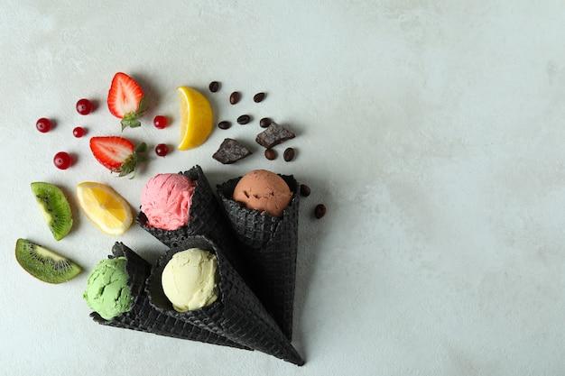 Cones pretos com sorvete e ingredientes em branco texturizado