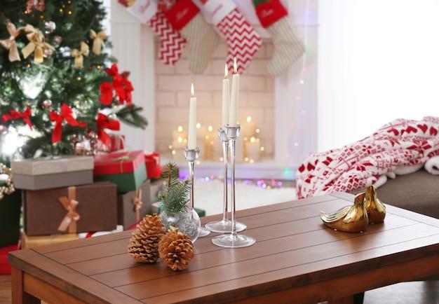 Cones, velas e decoração de natal em mesa de madeira contra lareira