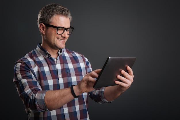 Conexão de internet. cara divertido e focado olhando um documento usando seu gadget e parado isolado em um fundo cinza