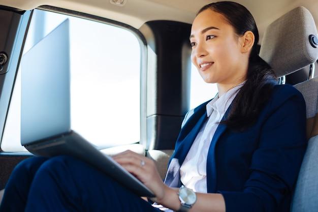Conexão de internet. mulher positiva e encantada usando a conexão com a internet enquanto trabalha no carro em seu laptop