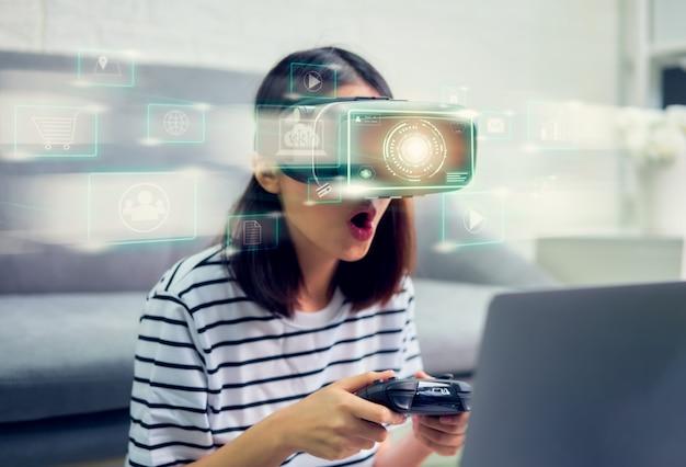 Conexão do conceito e interfaces de tecnologia digital, animado jovem mulher asiática usando um fone de ouvido da realidade virtual e joysticks, bela luz com linhas de cor.