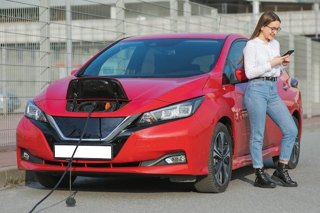 Conexão do plugue do carregador de um carro elétrico. a menina está com o telefone perto de seu carro elétrico e espera quando o veículo será carregado