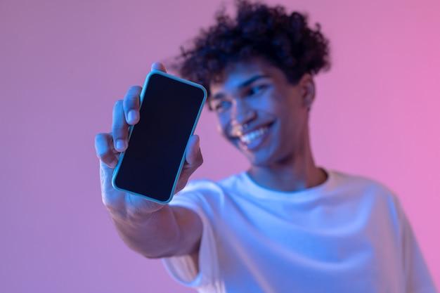 Conexão. foto de um cara sorridente de cabelos cacheados com um smartphone