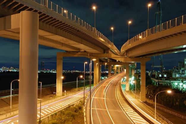 Conexão noturna de rodovia com estrada reta indo para longe, com traços claros de carros em movimento, tóquio, japão