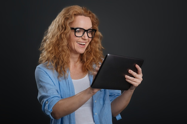 Conexão sem fio. mulher atraente, inteligente e dedicada olhando as páginas da internet e encontrando algo interessante enquanto usa seu tablet