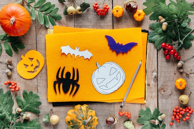 Confecção de decorações de feltro do dia das bruxas. halloween feito à mão de feltro, abóbora, aranha e enfeites de morcego