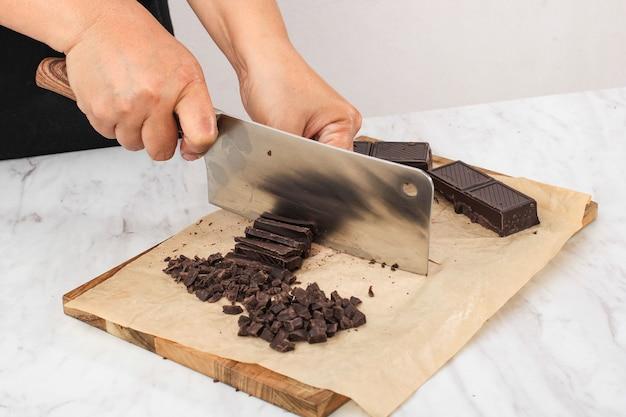 Confeitaria de doces e conceito de padaria culinária, mãos femininas com faca de cozinha picar barra de chocolate em pedaços na tábua de madeira no fundo branco