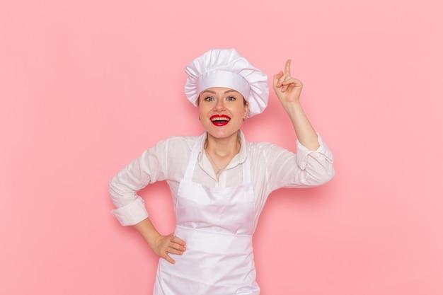 Confeitaria de frente para a confeitaria vestida de branco posando com uma expressão encantada na confeitaria de parede rosa claro trabalho de pastelaria doce