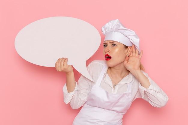Confeitaria feminina de vista frontal, vestida de branco, posando com uma placa branca, tentando ouvir na parede rosa confeitaria doce trabalho de pastelaria