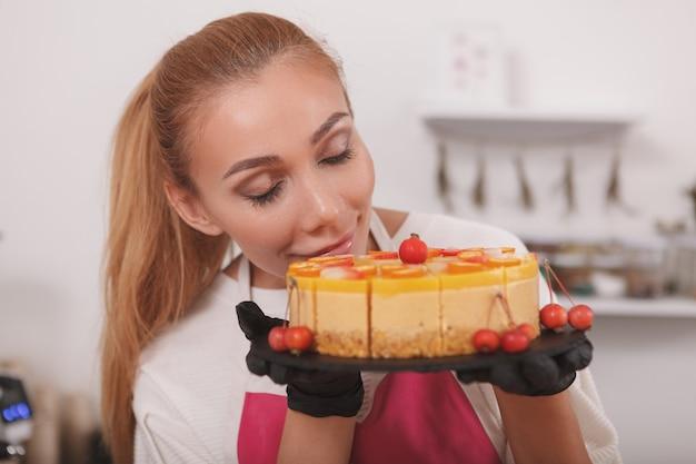 Confeiteira cheirando um delicioso bolo de manga cru que ela está vendendo em seu café