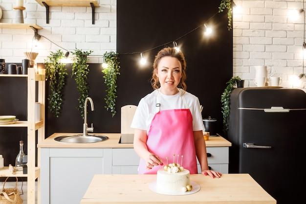 Confeiteira cozinhando bolo de aniversário na cozinha, dona de casa usando avental rosa