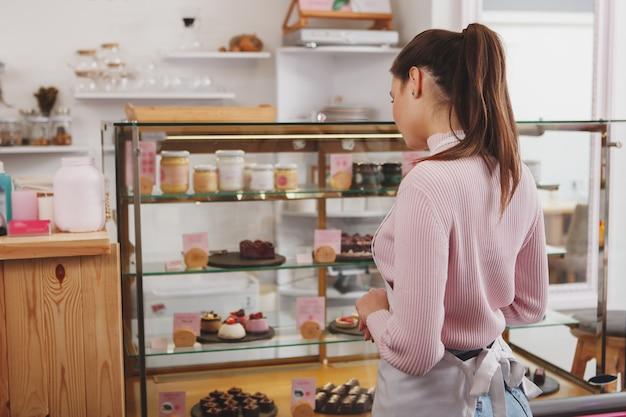 Confeiteira examinando a vitrine do café antes de abrir para os clientes