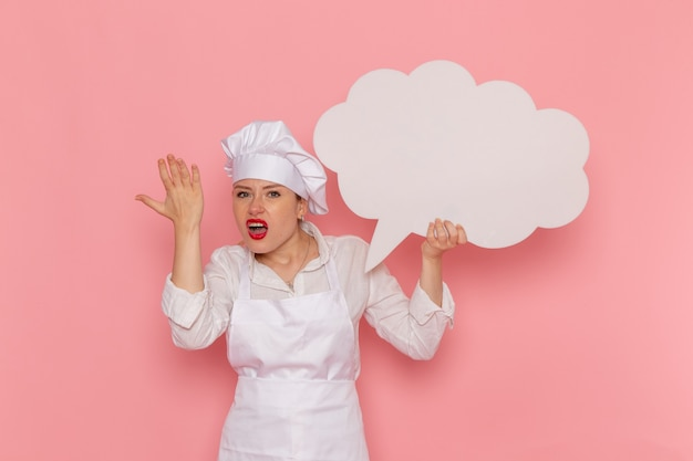Confeiteira feminina de vista frontal vestida de branco segurando uma grande placa branca na parede rosa claro.