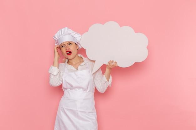 Confeiteira feminina de vista frontal vestida de branco segurando uma grande placa branca na parede rosa trabalho de cozinheiro cozinha cozinha comida