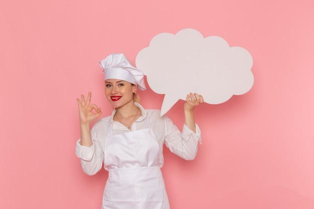 Confeiteira feminina de vista frontal vestida de branco segurando uma grande placa branca sorrindo na parede rosa trabalho de cozinheiro cozinha cozinha comida