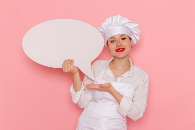 Confeiteira feminina de vista frontal, vestida de branco, segurando uma placa branca e sorrindo na mesa rosa, confeitaria, pastelaria doce, trabalho