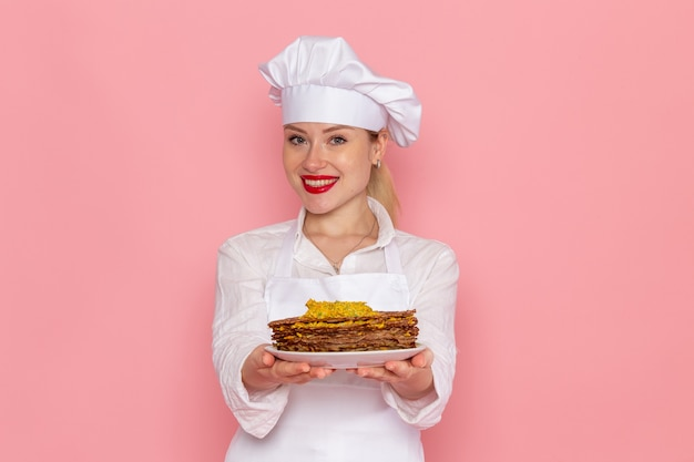 Confeiteira feminina em roupa branca segurando deliciosos pastéis sorrindo na parede rosa confeitaria de frente