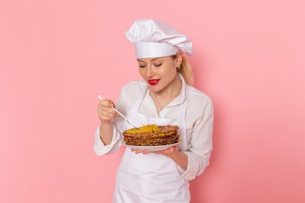 Confeiteira feminina vestida de branco segurando deliciosos doces e experimentando na parede rosa