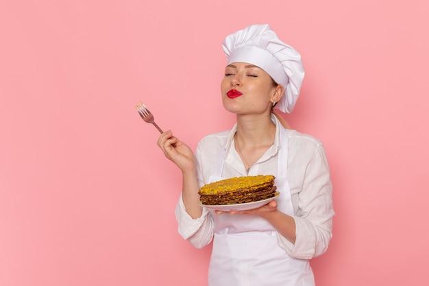 Confeiteira feminina vestida de branco segurando deliciosos pastéis e degustando-os na mesa rosa