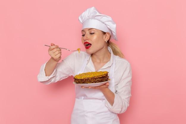 Confeiteira feminina vestida de branco segurando deliciosos pastéis e degustando-os na parede rosa
