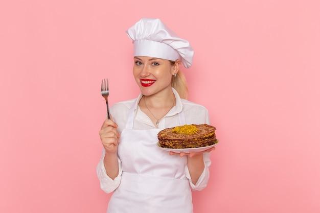 Confeiteira feminina vestida de branco segurando deliciosos pastéis na parede rosa claro
