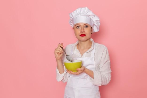 Confeiteira feminina vestida de branco segurando um prato verde com dovga degustando na mesa rosa comida refeição sopa de vegetais verdes