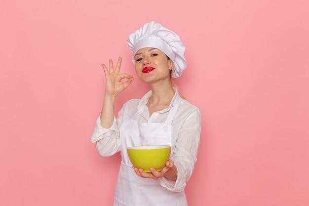 Confeiteira feminina vestida de branco segurando um prato verde com dovga na parede rosa comida refeição sopa de vegetais verdes