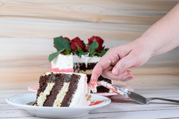 Confeiteira retirando a cobertura da fatia de bolo com o dedo. bolo de chocolate com recheio de mascarpone.
