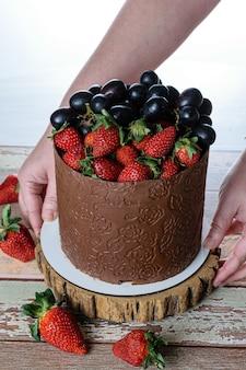 Confeiteiro colocando um bolo coberto de chocolate sobre a mesa, decorado com uvas e morangos.
