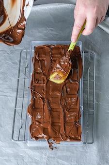 Confeiteiro com espátula para colocar o chocolate temperado em policarbonato.