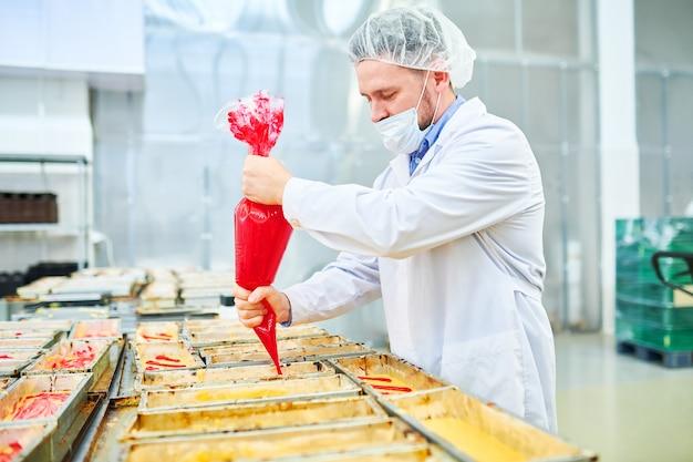 Confeiteiro concentrado usando saco de confeitar na fábrica
