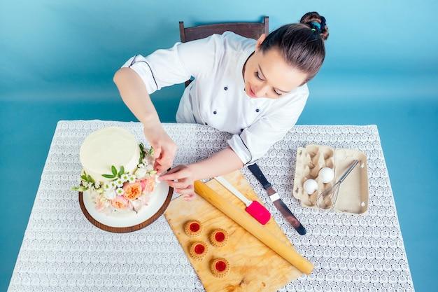 Confeiteiro confeiteiro chef padeiro mulher decora bolo de aniversário de casamento de duas camadas branco cremoso com flores frescas na mesa no estúdio sobre fundo azul. conceito de feriado e evento de preparação