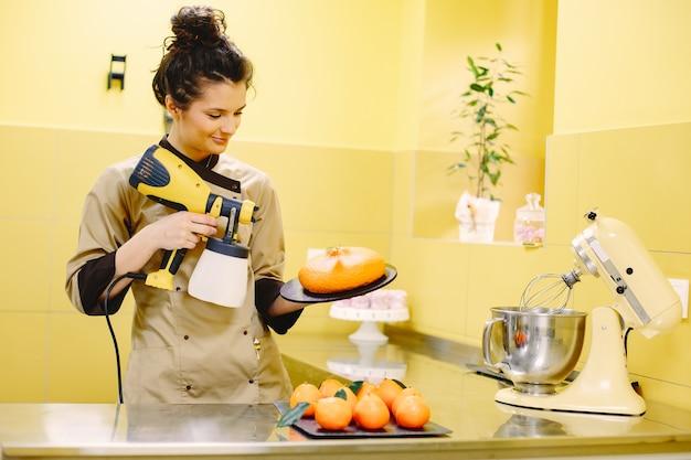 Confeiteiro de mulher com uma túnica. pasteleiro. senhora com ferramentas de cozimento.