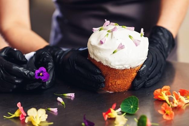 Confeiteiro decora o bolo da páscoa com flores delicadas.