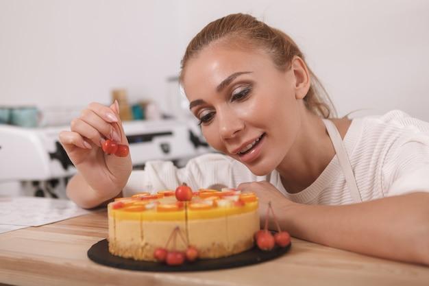 Confeiteiro enfeitando bolo vegano cru com cerejas