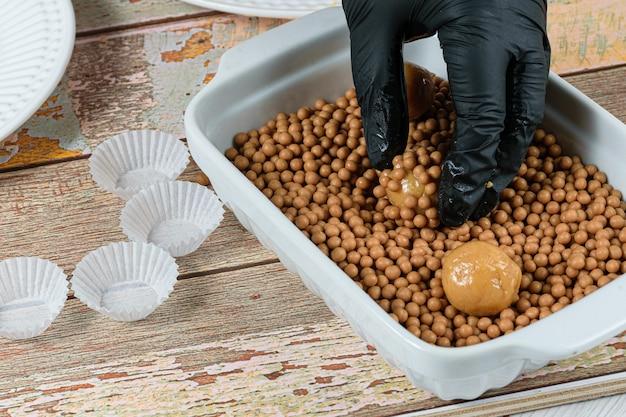 Confeiteiro enrolando o brigadeiro (brigadeiro) de doce de leite sobre caramelos salgados e crocantes.