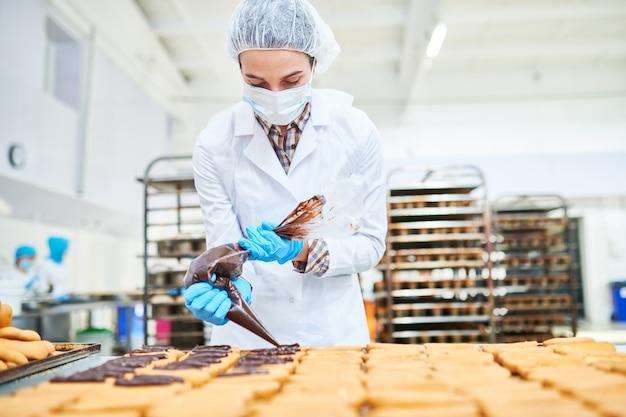 Confeiteiro, espremendo o creme de chocolate do saco de confeitar