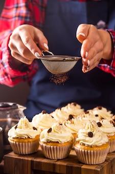 Confeiteiro feminino decora cupcakes com pó de cacau tiramisu