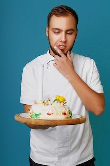 Confeiteiro masculino jovem em uma túnica com um bolo