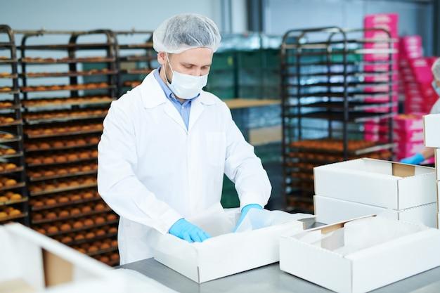 Confeiteiro na fábrica colocando pergaminho em embalagem vazia