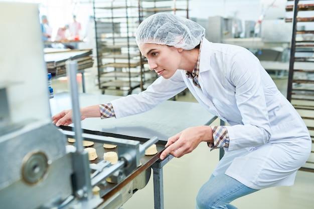 Confeiteiro, segurando a bandeja com pastelaria enquanto estiver operando a máquina