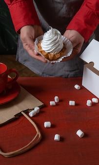 Confeiteiro segurando bolo branco perto da caixa de papel branco e uma xícara de café na mesa vermelha.