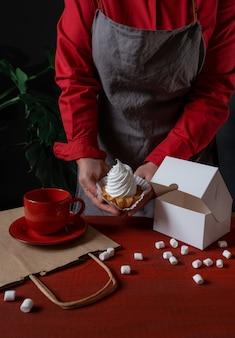 Confeiteiro segurando uma caixa de papel branco com bolo branco perto da mesa vermelha