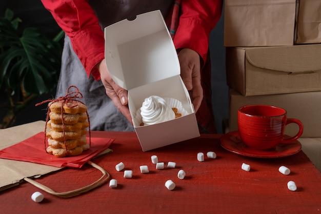 Confeiteiro segurando uma caixa de papel branco com bolo branco perto da mesa vermelha.