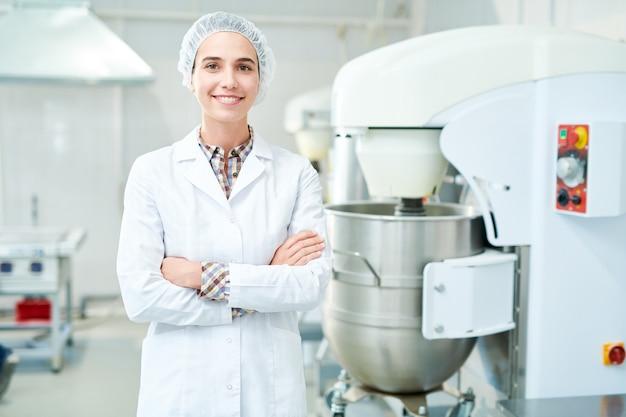 Confeiteiro sorridente em pé na fábrica