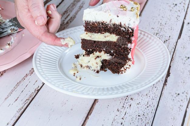 Confeiteiro tirando um pedaço de recheio do bolo. bolo de chocolate com recheio de mascarpone.