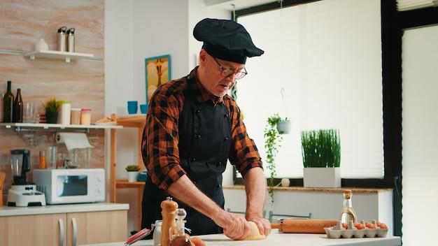 Confeiteiro trabalhando em casa com massa crua na cozinha moderna gravando a receita. padeiro idoso aposentado com bonete misturando ingredientes com farinha peneirada amassando para assar o pão tradicional.